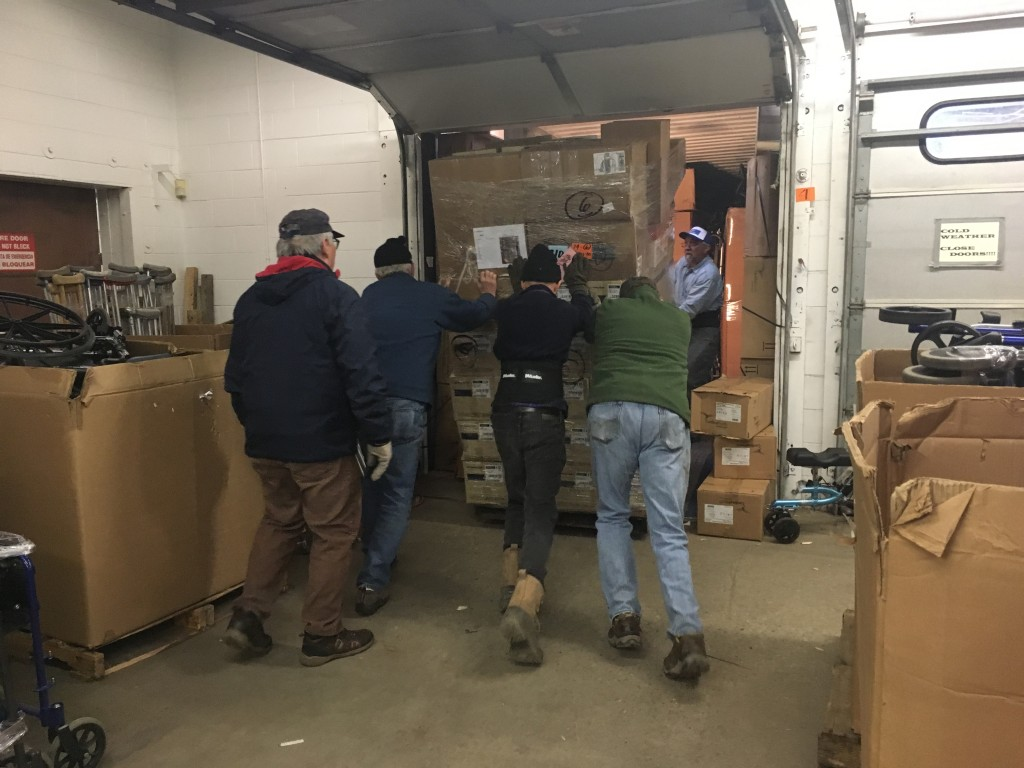 Volunteers loading a pallet of donated medical supplies onto a container, April 2018.